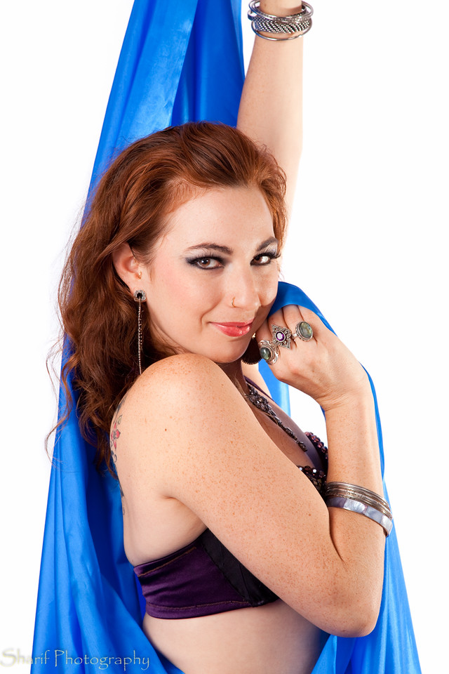 Belly dancer with blue veil looking coy