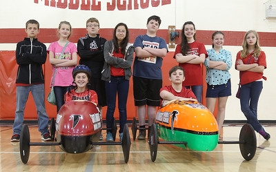 The South Amherst Middle School Soapbox Derby teams are all ready to go for the win. In the cars, from left, are Grace Sherban, 12 and Sam Solowiej, 13. Behind them are the crews, from left, Garrett Varndell, 12, Abigail Kerby, 12, Liam Lockhart, 13, Anne Bartish, 13, Jaidyn Keene, 13, Abby Landreth, 13, Leah Harris, 12, Emily Campbell, 12. BRUCE BISHOP/CHRONICLE