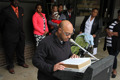 ANNA NORRIS/CHRONICLE Eli Delisantos reads from the Book of Genesis as the Elyria Ministerial Alliance kicked off the National Bible Reading Marathon on Sunday afternoon, May 1, in front of the Lorain County Administration Building in Elyria.