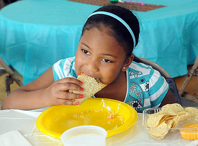Brooklyn Marberry, a first grader at Franklin Elementary, has a taco at the annual Elyria Public Schools Cinco de Mayo Fundraiser at Nick Abraham Elyria Ford in Elyria on Tuesday, May 3. STEVE MANHEIM/CHRONICLE