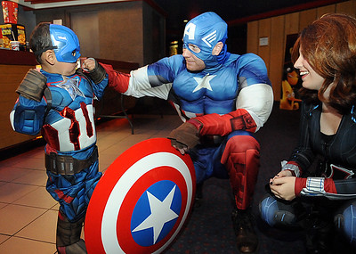Jordan Matear, 3, of Elyria, left, meets Andy Bryne as Captain America and Mandy Shultz as Black Widow at Atlas Cinemas at Midway Mall on Friday, May 6.  They are members of Super Heroes to Kids in Ohio.  STEVE MANHEIM/CHRONICLE
