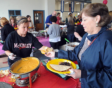 McKinley Elementary principal Jen Fitch, left, serves Donna Filipiak of Elyria at the annual Elyria Public Schools Cinco de Mayo Fundraiser at Nick Abraham Elyria Ford in Elyria on Tuesday, May 3.  STEVE MANHEIM/CHRONICLE