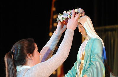 Kathryn Scarvelli, a senior at Elyria Catholic, crowns a statue of Mary, at the May Crowning ceremony at Elyria Catholic High on Monday, May 2. STEVE MANHEIM/CHRONICLE