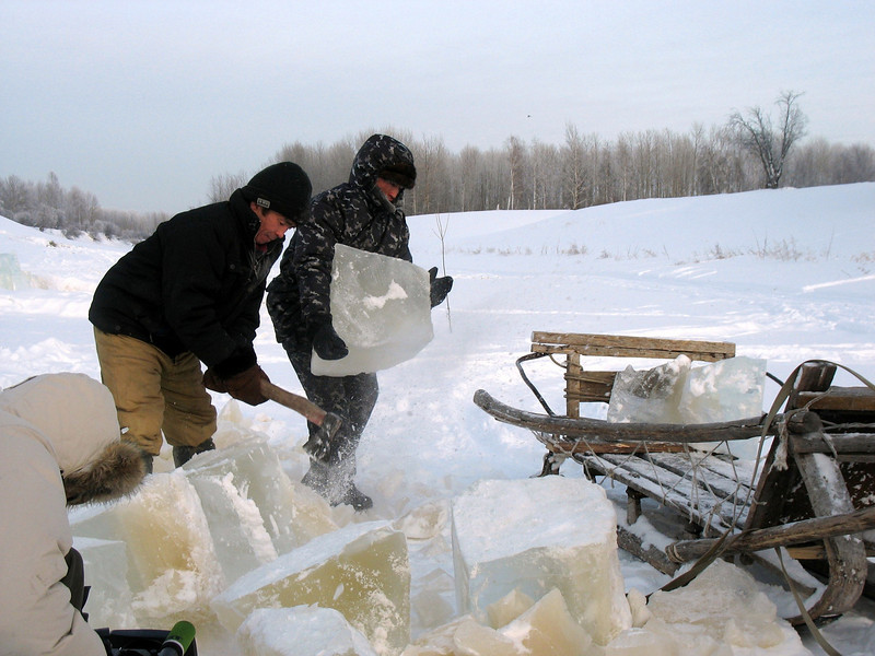 Chopping blocks of ice to take home for water. (Laytamak, Siberia, Russia)