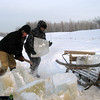 Chopping blocks of ice to take home for water. (Laytamak, Siberia, Russia)