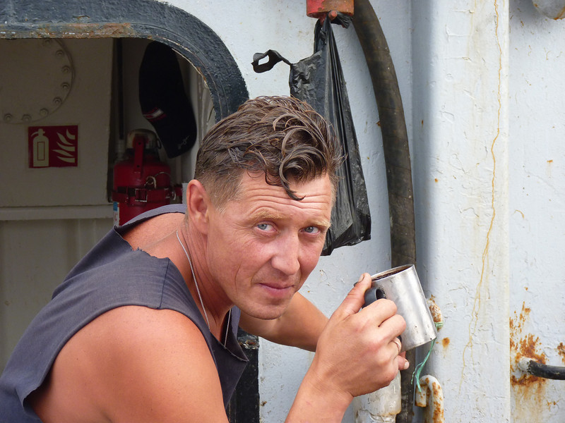 While the Border Patrol checks his boat, this fisherman takes time out for a coffee break. (Off Sakhalin Island)