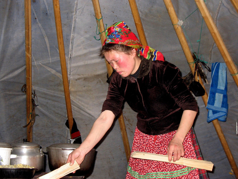 A woman's work is never done. Nenets woman, Svetlana, firing up the stove in her chum [tent]. (Nenets Autonomous District, Russia)