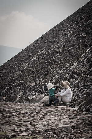 A mother and child rest climbing up the Temple of the Sun