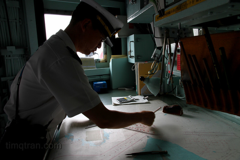 The navigator of the JS Hiei plots our course after sailing out of Yokosuka.
