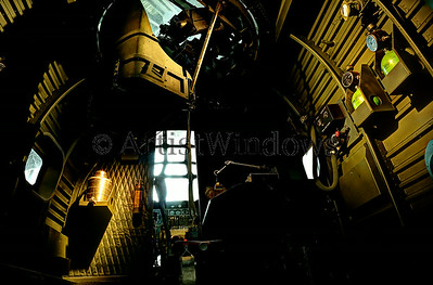 Looking inside a flying fortress B52 with the pilot and co-pilot up front.  Upper gunner set and machine gun up top.
