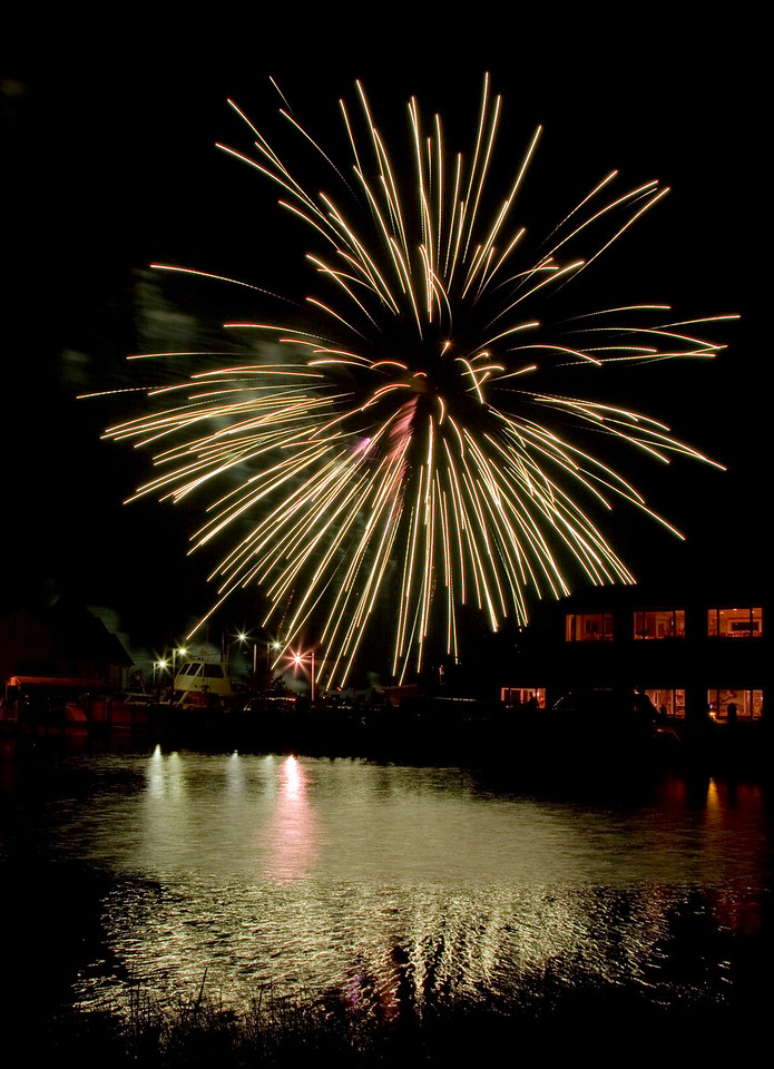 4th of July Fireworks at Solomon's Island in Southern Maryland. The lighted building is Stoney Kingfisher's Restaurant