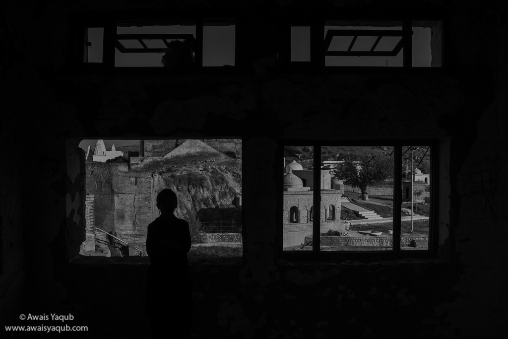 Boy poses infront of window inside ruined part of Katas Raj Temples located around 120km from Islamabad