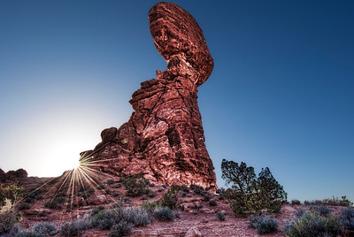 Balance Rock at Arches National Park.  The sun drops below its shoulder on a cloudless evening.
