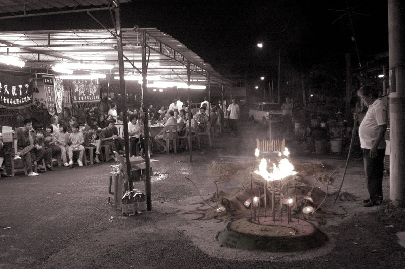 I took this picture to show an overview of my grandma's funeral process. <br /> <br /> On that night, relatives and friends were sitted on the left while the priest's assistant prepares the fire on the right.