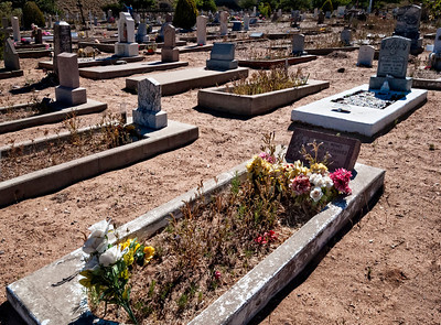 Sand, flowers and weeds.  Cemetery at Albuquerque, New Mexico.