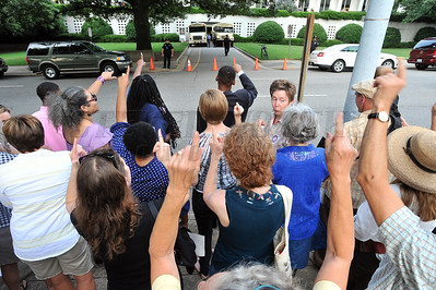 Protesters gathers across from the North Carolina General assembly building awaiting the first glimpse of one of the 120 people arrested inside and transported to awaiting NC Division of Prison buses.  People gathered in the Halifax Mall in Downtown Raleigh on June 24, 2013 to protest the policies and laws proposed and passed by the North Carolina State General Assembly.