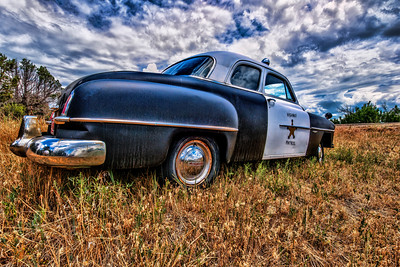 In Bayfield, Colorado, an old Sheriff car was parked in the summer grass.