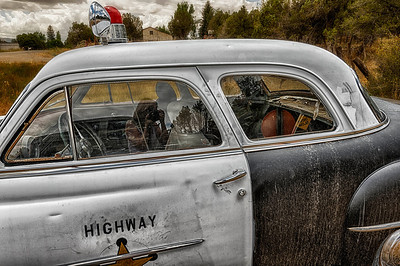 The reflections in the Highway Patrol car parked in Bayfield, Colorado reveal, among other things, the photographer.
