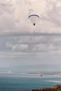 Hang gliders hover under the clouds near California State University at San Diego.