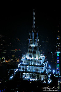"In this closeup we show you the top of the Jin Mao skyscraper highlighting its design theme of pagodas as desired by its Chinese owners. Like a Christmas tree point this beautiful detail sits atop the 88 stories making it even taller. The Istanbul-like tower to its right with a series of spheres is the world famous Oriental Pearl Tower once the tallest structure in Shanghai and now looking short by comparison.  ""Like Our Page"" for frequent updates  Asia photo shoot"