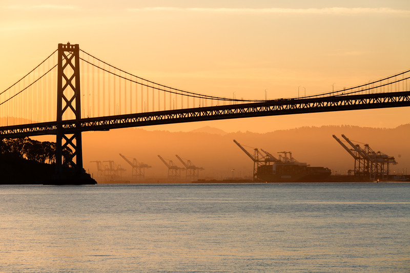 Shipping cranes in Oakland with the San Francisco - Oakland Bay Bridge in the foreground. Taken from the end of Pier 7.