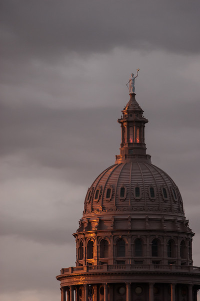 Texas State Capitol lit by the setting sun framed by storm clouds.