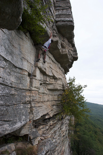 A buddy of mine climbing at the Shawangunks or simply the Gunks.  The route is called Shockley's Ceiling.  The move he's doing in photo is the crux (or toughest move) in the route.  When I did that same move, I fell, but luckily rope caught me.  Long story short, I finally climbed my way out of it an hour later.