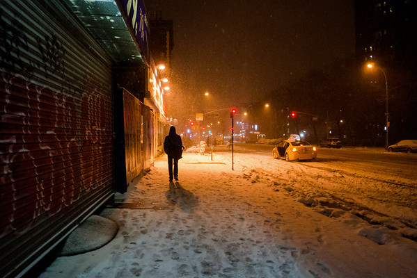 <h2>New York Winter Night - East Village Graffiti and Snow</h2> - By Vivienne Gucwa  A person walks down a sidewalk covered in snow next to a storefront covered in graffiti in the East Village, a neighborhood in lower Manhattan as snow falls and blankets New York City at night.  ---