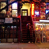 <h2>St. Mark's Place at Night - East Village - New York City</h2> - By Vivienne Gucwa <br><br>  When the days concede to night in the winter, there is a certain comfort in the glow of neon city lights. <br><br>  This particular view is of St. Mark's Place in the East Village. The cow belongs to the restaurant Mark and the neon belongs to Andromeda Tattoo and Piercing. The sign that is partially concealed is Rockit Scientist Records which was a great records store that dated back to the mid 1990s when the East Village was home to far more records stores and had a more eclectic vibe.  <br><br>  There is a coldness to neon that is eclipsed by a peculiar sort of warmth when the windchills dip into the single digits. It's a sign of life. People tend to huddle under the glow of the lights in the winter with a frequency that isn't seen as much in warmer months as if they are city moths drawn to the glowing promise of warmth. <br><br>  --- <br><br>