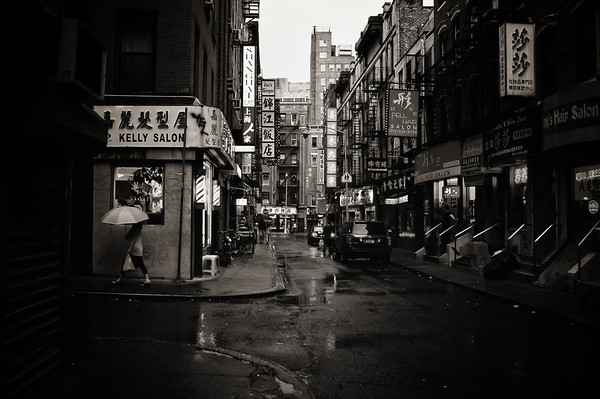 <h2>Rain on Pell Street - Chinatown - New York City</h2> - By Vivienne Gucwa  In-between light creates all its own stories. It's the light after a long night when the city sleepily shakes off the blanket of darkness and stretches in the first few rays of the waking sun and it's also the light after a long day when the city unwinds basking in the low light of dusk.  In-between light caught in the steady drizzle of rain is even more enchanting. Tears of laughter, heartache, sorrow and joy fall on the city streets silencing their hungry rumble. Buildings darken one by one as the city blurs softly preparing for its nightly refractory period.  ---