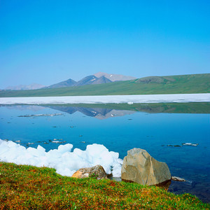 North America, USA, Alaska, ANWR, Ice on shore of  icy Schrader Lake looking to Okiotak Peak in Third Range, July 1990
