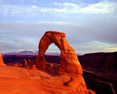 Delicate Arch in Arches National Park with snow topped La Sal mountains in distance, near Moab, Utah