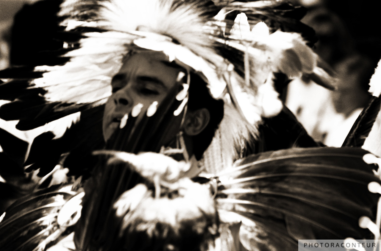 """Dances with Feathers"" ~ Native American engrossed in extensive feathered regalia at a pow-wow."