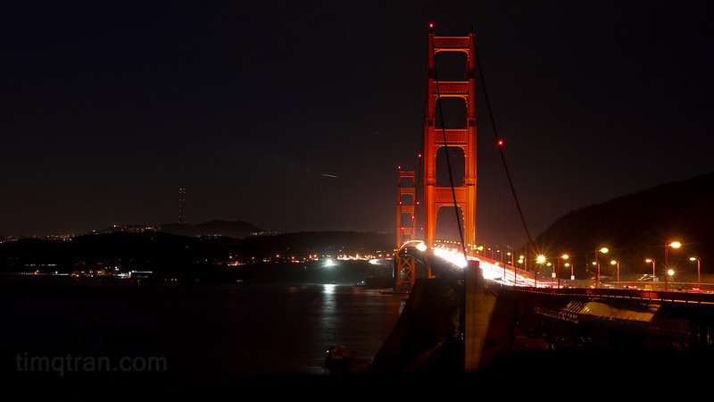 The Golden Gate Bridge at night, carrying hundreds of gleaming cars across the Bay.