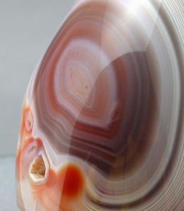 Lake Superior Agate. Note the crystal impression (lower left). Again, what appear to be fractures running up the face and branching out at the top are simply edges of reflections. Someone did an outstanding job of polishing this rock - the face and banding are remarkably smooth and clear.
