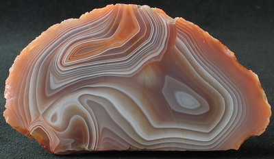 """Lake Superior Agate; 2.4oz. 8.5cm x 4.6cm x 1.5cm.  A """"slab"""" that has been face polished. It's a fine rock, and an excellent example of agate formation - note what appear to be pour holes at the top. It is likely that hot molten silicates flowed into a basalt cavity and as they cooled formed distinct layers - what we now call """"banding."""" Why they flow the directions they flow, create various shapes and thicknesses, and produce bands of very distinctive colors from the rest is still a mystery of science."""