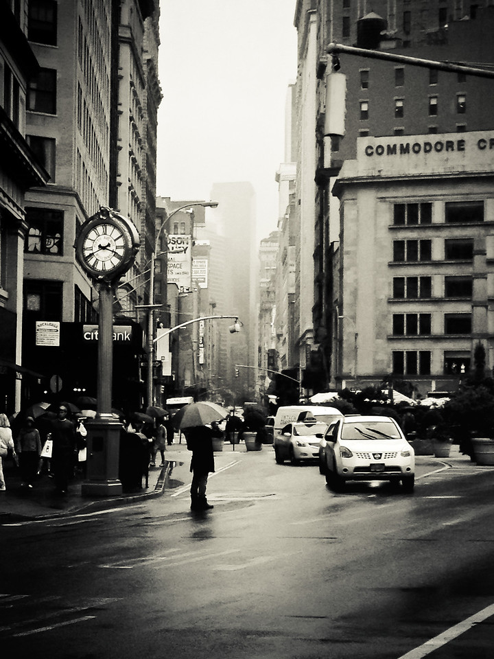 <h2>New York City - Rain</h2> - By Vivienne Gucwa  There is an inherent romance that buzzes through the air in New York City when it rains.   The Flatiron District is one of my favorite areas in Manhattan when it rains. The street (5th Avenue) opens up to reveal distant skyscrapers that disappear into heavy fog as people weave their way through the multitudes of umbrellas.    The clock in this image is the Fifth Avenue Building Clock which is a New York City landmark and recalls another era: one where these ornamental clocks played a role in attracting people to gilded era storefronts. This vantage point is with the Flatiron Building directly in back of the viewer looking up 5th Avenue.  ---
