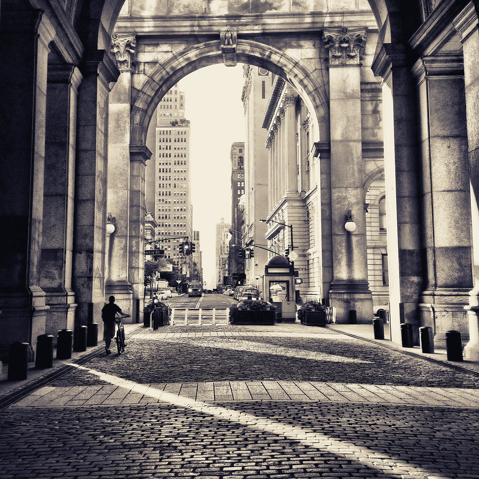 <h2>Municipal Building - New York City - Towards the Light</h2> - By Vivienne Gucwa  We move slowly towards the light over the cobblestones that the weary feet of all those who have passed over these same paths have passed before us. And through the archways and doors that sit in our immediate view, the city opens up like so many opportunities that sit every so slightly out of our reach.