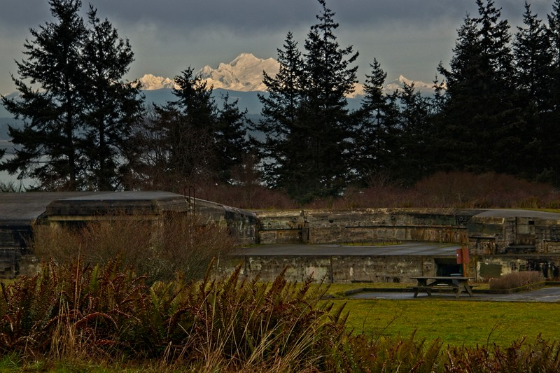 Cascade peaks endure over remains of a WWII bunker at Fort Worden in Washington.<br /> ©Carl Clark
