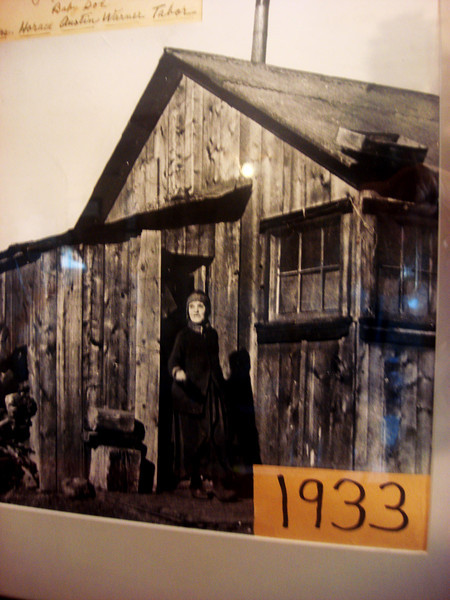 Baby Doe Tabor in front of her house next to the Matchless Mine