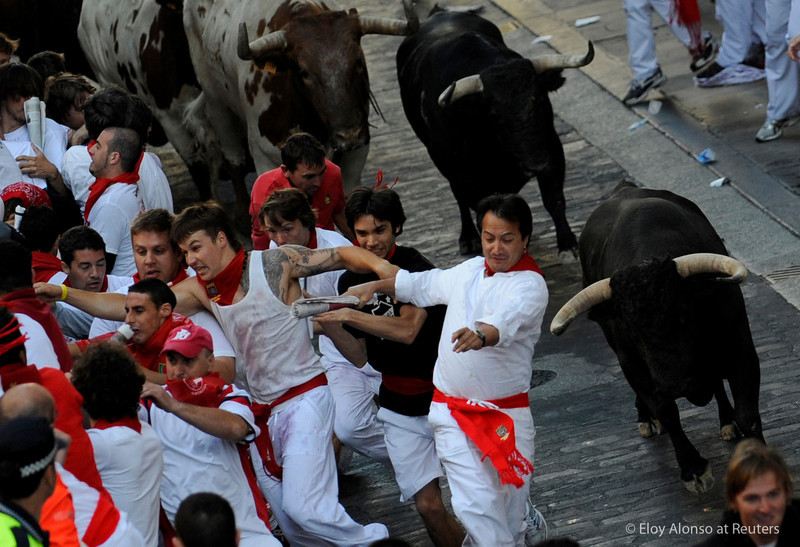 Runners are chased by Alcurrucen fighting bulls on the first day of the running of the bulls at the San Fermin festival in Pamplona July 7, 2009. Six bulls are released every morning at 8:00 through the cobbled streets of Pamplona to the bullring, where they will be killed in a bullfight in the afternoon. REUTERS/Eloy Alonso.