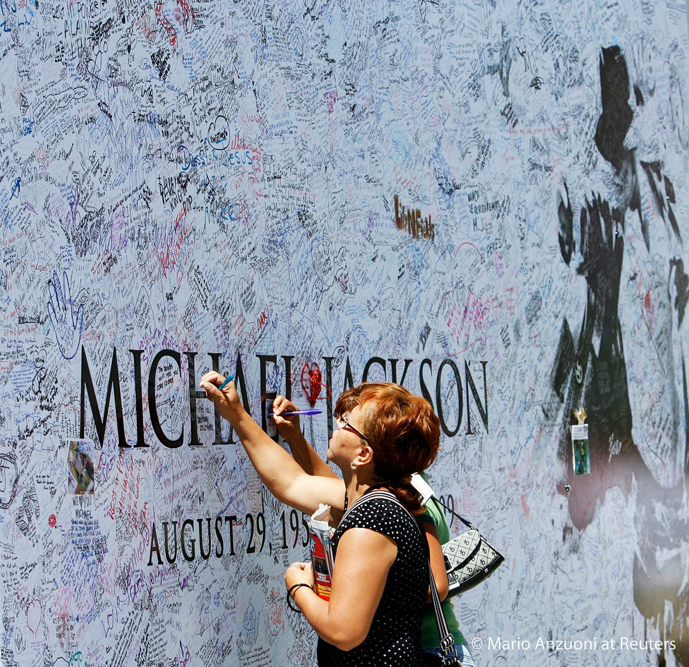 Fans sign a large Michael Jackson poster outside Staples Center in Los Angeles July 6, 2009. The memorial for the pop star will be held at Staples Center in Los Angeles July 7.  REUTERS/Mario Anzuoni
