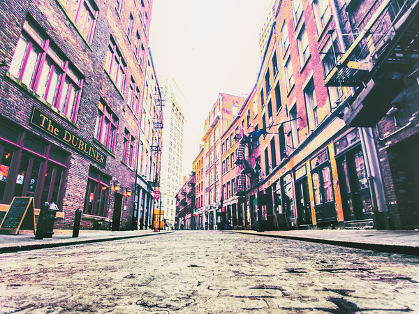 <h2>Stone Street - New York City</h2> - By Vivienne Gucwa  Stone Street is a narrow cobblestone alley that was first developed by Dutch colonists in the 1600s. Its claim to fame is that it is New York City's first paved street and as such it is recognized as a historic landmark.   It's the main part of an area currently known as the Stone Street Historic District. Nestled among skyscrapers in the Financial District, it's something of a time machine back into another era of New York City's history. The street is the site where British merchants traded and sold goods, where American colonialists passionately spoke of independence and where tracts of land were purchased and sold (completely disregarding the earlier inhabitants of the area).  The Dutch West India Company first sold this area to European property owners in the mid 1600s. It was around 1658 that the street was paved. The name Stone Street actually came about in the late 1700s. Prior to being named Stone Street, this alley was called Hoogh Straet and then Brouwer Street and also spent some time as Duke Street. Since the street is so close to the waterfront, it was the site of a tremendous amount of commercial activity for two centuries.  In the mid 1800s, the area was destroyed by the Great Fire. Even though the Great Fire leveled hundreds of buildings in the area, the Stone Street district bounced back due to New York City having the leading maritime port in the country. However, in the mid twentieth century the area saw a decline due to maritime activity moving to the west side of Manhattan. In the mid 1990s, funding was secured to restore the area back to its former glory.   ---