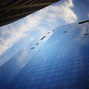 <h2>Where I End And You Begin - Skyscraper - New York City</h2> - By Vivienne Gucwa  When the wind is still, the sky seduces the city with a reverie of itself poured onto the glass of skyscrapers like a liquid dream emulsion.  The fine feathered touch of the clouds brush lightly against the the cool skin of structures reaching towards the distant comfort of loftier aspirations and shadows cast on the world below muffle the quickened heartbeats and soft sighs of this not-so-clandestine meeting.  ---  Despite all my protestations about glass buildings rising in the place of other more ornate and classic works of architecture, I will say that if you find yourself looking up at the newer glass buildings on a beautiful day, the views are beautiful.  ---