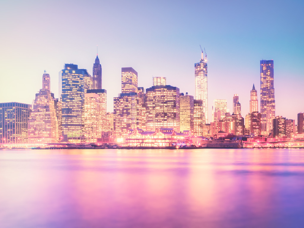 <h2>New York City - Night Skyline</h2> - By Vivienne Gucwa  Dusk dances on the water  every evening  as the city hangs  brightly in a night sky  illuminated by the lights  of skyscrapers that   climb their way up  to the surface of   dreams.  ---  The moments between day and night are some of my favorite moments. The sky seems to linger and dwell in the hues of the day while the city's lights mix with the colors of the recent sunset on the surface of the water. This image was taken on a brisk night while standing in Brooklyn Bridge Park. The view is of the skyscrapers of lower Manhattan including 1 WTC (also known as the Freedom Tower, the Woolworth Building, and New York by Gehry.  ---