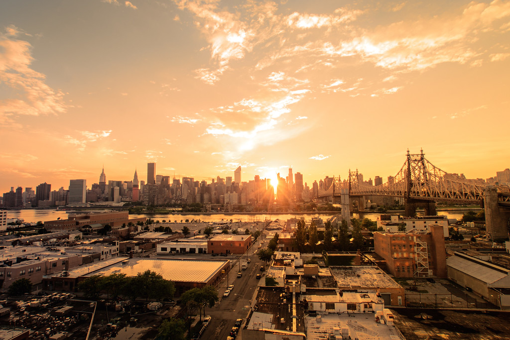 <h2>New York City Sunset </h2> - By Vivienne Gucwa<br><br>   Sunsets are skipped heartbeats:<br><br>  full of light and suspended in time, <br><br>  they are the trailed off, long ends<br><br>  of phrases uttered <br><br>  by the city and sky<br><br>  when their faces are close <br><br>  and kisses are imminent.<br><br>   ---<br><br>  This is a view of the skyline of midtown Manhattan including the Empire State Building and the Chrysler Building. It was taken during a brilliant sunset that emerged after a rather dramatic rainstorm. The rooftops in the foreground are the rooftops of Long Island City, Queens. To the right is the Queensboro Bridge (also known as the 59th Street Bridge, and the Ed Koch Queensboro Bridge). <br><br>  ---<br><br>