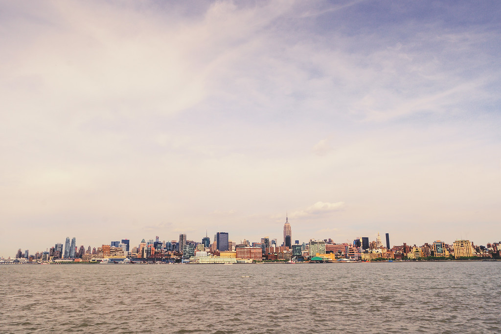 <h2>New York City Skyline Cityscape</h2> - By Vivienne Gucwa  The city rises out of the water   proud, elegant  adorned in its colorful, man-made suits of armor.  And all of the hopes and dreams  billow up to meet the sky  propelling themselves past   the places and spaces that   hold them.  ---  This was taken recently while on a boat to New Jersey. As I have mentioned before in other posts, one of the many reasons I love living in New York City is that the shifts in perspective can be so incredibly jarring and thought provoking. When you are in the midst of it all, you don't fully realize that Manhattan (in particular) is an island.  And yet, once you get on any of the boats that traverse the rivers that surround the city, it's really overwhelming to see Manhattan's skyline shrink into the distance under a vast sky.  The Hudson River is all that sits between parts of New Jersey and Manhattan. This view includes the Empire State Building and the midtown Manhattan skyline that sits on the west side of the island.   ---