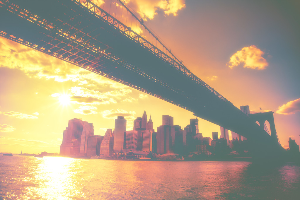 <h2>The New York City Skyline and the Statue of Liberty at Sunset - Under the Brooklyn Bridge </h2> - By Vivienne Gucwa<br><br>  Every evening, the sun slides slowly down along the sky gleaming and floating above the city.<br><br>  Reaching through the clouds to look at its reflection of liquid gold in the water below, it pauses.  <br><br> And in those brief moments, it's as if the earth has stopped revolving just long enough for the sun and the city to kiss.<br><br>  ---<br><br>  This was taken while on a boat in the East River passing under the Brooklyn Bridge. The skyline is the lower Manhattan skyline featuring the skyscrapers of the Financial District and Pier 17 at South Street Seaport. To the left in the distance, sits the Statue of Liberty.<br><br>  ---<br><br>