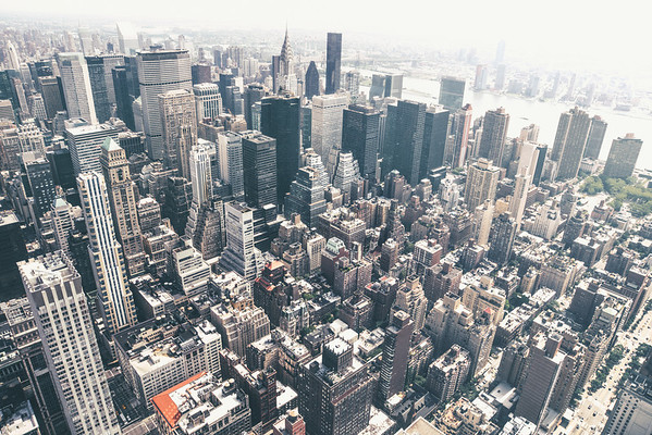 <h2>New York City Skyline - Skyscrapers of Midtown Manhattan from Above</h2> - By Vivienne Gucwa<br><br>  Late summer light<br><br>  hangs over the city:<br><br>  humid-laden heartache<br><br>  tinged with heavy hope<br><br>  and hazy promises.<br><br>   Where the winter brings a crystal sharp clarity to New York City, the summer seems to bring with it a gorgeous, bittersweet gauze-like haze. Summers in New York City cling to the ribs and heart like ethereal remnants of distant thoughts peeking their heads out of the sea of heat and humidity. <br><br>  ---<br><br>  This is a view of the roof tops, skyscrapers, water towers and streets of midtown Manhattan as viewed from above. <br><br>   ---<br><br>