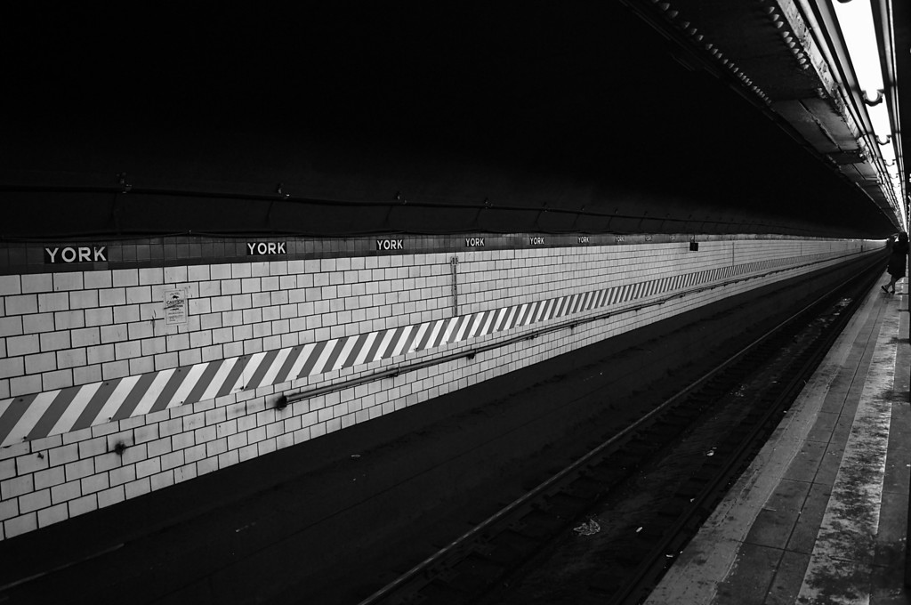 <h2> Waiting - Train Station - New York City </h2> - By Vivienne Gucwa  We wait.  We wait for the city to move beneath our feet.  We wait for the universe to rise up from under the weight of our own gravitas; the movement of our world spinning on its axis.  And while we wait, the plaster crumbles, the paint peels, the train tracks rust; all suspended in their own decay like flies in amber.  We wait because it's the only way to slow down as time pushes us forward further and further into the vast expanse of eternity.  We wait for the train to come.  ---